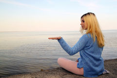Young girl sitting on the beach with an open hand Royalty Free Stock Image