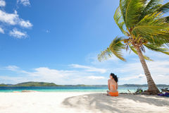 Young girl sitting on beach under coconut tree Stock Photos