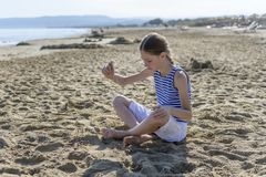 Young girl is sitting on the beach royalty free stock image