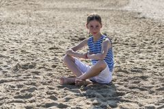 Young girl is sitting on the beach stock photo