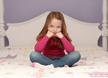Young girl sitting on bed. Posing for a portrait Royalty Free Stock Images