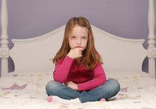 Young girl sitting on bed Stock Images