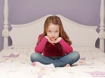 Young girl sitting on bed royalty free stock images