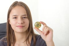 Young girl sitting on bed. Holding a bitcoin Royalty Free Stock Photo
