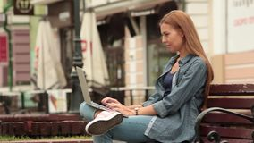 Young girl sitting on a bench in the city and working on a laptop. stock video footage