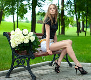 Young girl sitting on a bench in a large bouquet o Royalty Free Stock Image