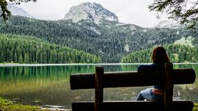 Young girl sitting on a bench and looking at the black lake in the national Park Durmitor. Montenegro. royalty free stock image