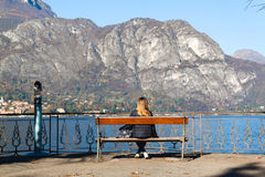 Young girl sitting on a bench looking at lake and mountains Royalty Free Stock Photo