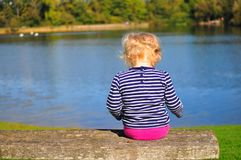 Young girl sitting on bench overlooking lake royalty free stock images
