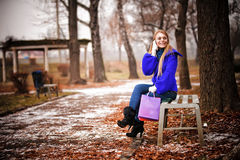The young girl sitting on a bench in park Stock Photos