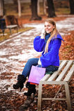 The young girl sitting on a bench in park Stock Images