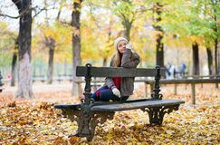 Young girl sitting on a bench in park Stock Photo