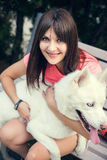 Young girl sitting on the bench and playing with her white husky dog Stock Photos