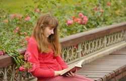 Girl is sitting on bench and reading book,  autumn. Young girl is sitting on bench and reading book, outdoors, autumn Stock Photography