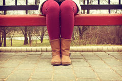 Young girl sitting on a bench in red pants and brown boots Stock Image