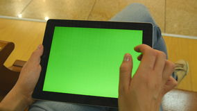 Young girl sitting at bench in shopping mall and working with tablet. Female hands using tablet pc with green screen stock video