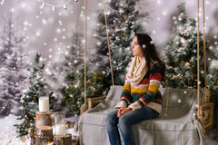 Young girl sitting on a bench or a swing in a snow-covered park Stock Image