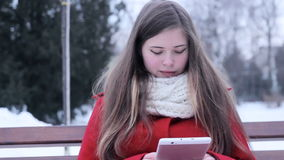 Young girl sitting at bench and watching tablet pc stock video