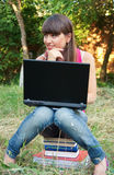 Young girl with sitting on the books with a laptop Royalty Free Stock Photography