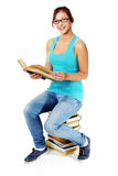 Young girl sitting on books and smiling. Royalty Free Stock Image