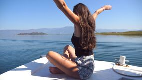 Young girl sitting on bow of boat, looking to beautiful nature landscape and raising hands to enjoy freedom. Happy woman. Enjoying summer travel. Vacation or stock footage