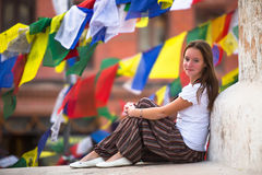 Young girl sitting on Buddhist stupa, prayer flags flying in the background. Travel. Stock Photo