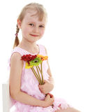 Young girl sitting with a bunch of flowers. Cute girl with pigtails, sitting holding a bouquet of flowers.Isolated on white background Stock Image