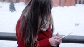 Young girl sitting at bus stop and watching tablet pc stock video footage