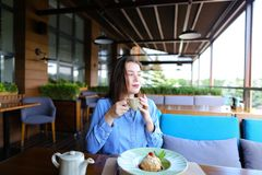 Cheerful girl browsing by smartphone at cafe and eating desser. Young girl sitting at cafe, browsing by smartphone and eating dessert with cup of tea on table royalty free stock image
