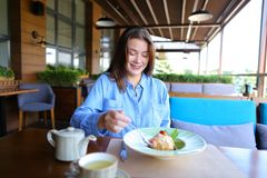 Cheerful girl browsing by smartphone at cafe and eating desser. Young girl sitting at cafe, browsing by smartphone and eating dessert with cup of tea on table royalty free stock images