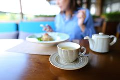 Cheerful girl browsing by smartphone at cafe and eating desser. Young girl sitting at cafe, browsing by smartphone and eating dessert with cup of tea on table royalty free stock photography