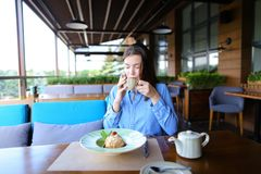 Cheerful girl browsing by smartphone at cafe and eating desser. Young girl sitting at cafe, browsing by smartphone and eating dessert with cup of tea on table stock images