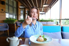 Cheerful girl browsing by smartphone at cafe and eating desser. Young girl sitting at cafe, browsing by smartphone and eating dessert with cup of tea on table stock photo
