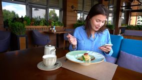 Cheerful girl browsing by smartphone at cafe in and eating desse. Young girl sitting at cafe, browsing by smartphone and eating dessert with cup of tea on table Royalty Free Stock Image