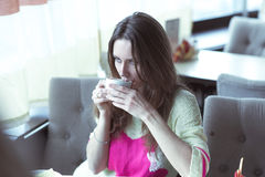 Young girl, sitting in a cafe with cup of coffee. Beautiful young woman in a fashionable sweater, drinking hot coffee or tea while sitting in a cafe and looks Royalty Free Stock Image