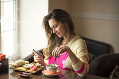 Young girl, sitting in a cafe with cup of coffee. Young happy woman eating sushi for lunch at a small cafe and a healthy lifestyle, working on a smartphone Stock Photos