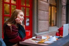 A young girl sitting in a cafe, holding a mug and smiling with an open laptop. Outside. In the autumn. A sweet young European girl sitting in a cafe hiding Stock Photo
