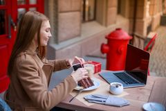 A young girl sitting in a cafe with a laptop and is photographing her dessert on a mobile phone. royalty free stock photography