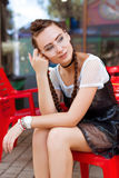 Young girl sitting in a cafe and smiling. Beautiful girl with glasses in a cafe smiling Stock Photo