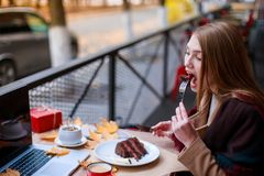 Young girl sitting in a cafeand eating a chocolate dessert. Outside. In the autumn. Young brunette girl sitting in a cafe hiding behind a warm blanket and Royalty Free Stock Photos
