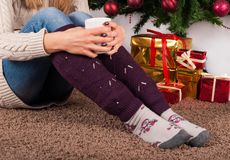 Young girl sitting on carpet floor and holding cup of coffee in hands on legs with warmers and Christmas tree and gift boxes in ba. Young female legs with Stock Photography