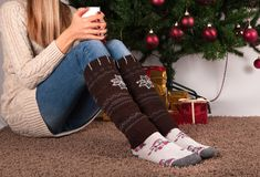 Young girl sitting on carpet floor and holding cup of coffee and warms socks on legs, in background is Christmas tree and present. Young female legs with warmers Stock Photo