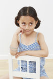 Young girl sitting on chair Stock Images
