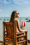 Young girl sitting on a chair near the sea Stock Photo
