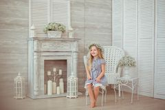 A young girl is sitting on the chair in the room Royalty Free Stock Photo