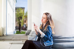 Young girl sitting on the college campus yard listening music. Young girl sitting on the college campus yard listening to the music on the smartphone Stock Image