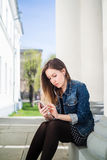 Young girl sitting on the college campus yard listening to music. Young girl sitting on the college campus yard listening to the music on the smartphone Royalty Free Stock Images