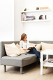 Young girl sitting on a couch in a bright room. And reading a magazine Royalty Free Stock Images