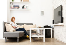 Young girl sitting on a couch in a bright room. And watching TV Stock Image