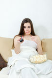 Young girl sitting on the couch at home and the list of programs Stock Images